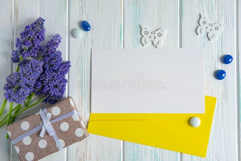 Purpurrote Blumen auf einem h?lzernen Hintergrund mit einem Geschenk Fahne mit Blumen der purpurroten Farbe, des Geschenks und de lizenzfreie stockfotografie