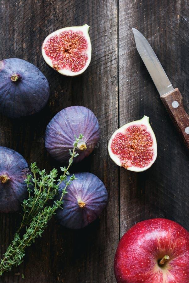 Purpurrote Feigen, roter Apfel und frischer Thymian auf Holztisch stockfotografie
