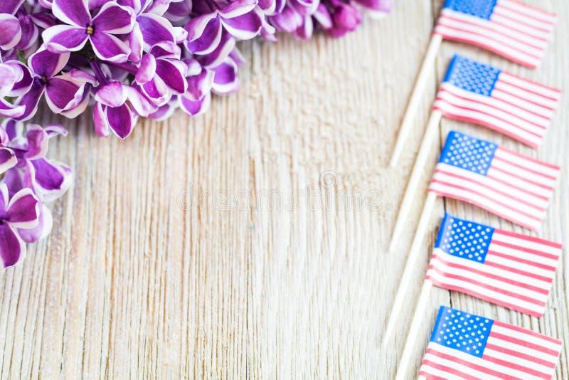 Purpurrote Flieder und Miniaturflaggen auf hölzernem Brett mit Raum für Kopie lizenzfreie stockfotografie