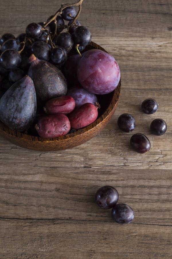 Purpurrote Frucht in einer hölzernen Schüssel lizenzfreie stockfotos