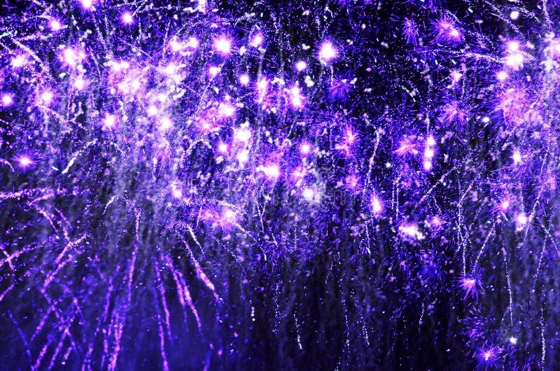 Purpurrote funkelnde Feuerwerke, die im Himmel der dunklen Nacht explodieren stockfotografie