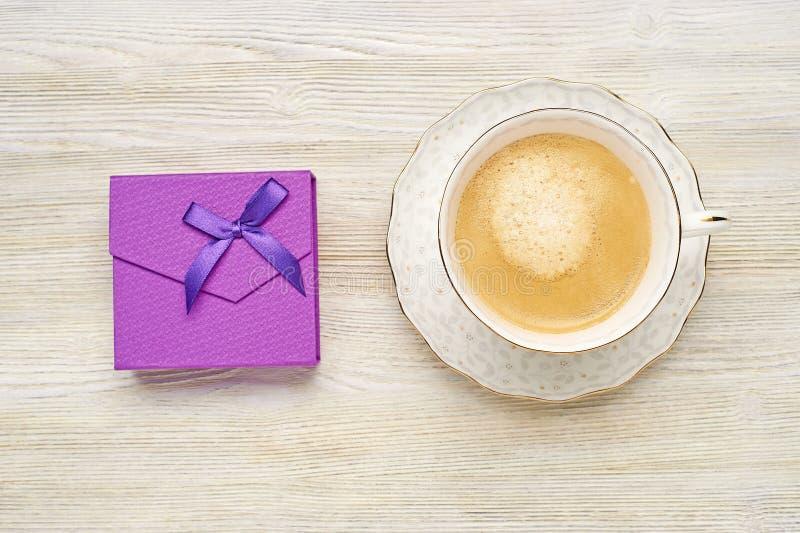 Purpurrote Geschenkbox mit Bogen und Cappuccino Schale auf einem hellen hölzernen Ba stockfoto