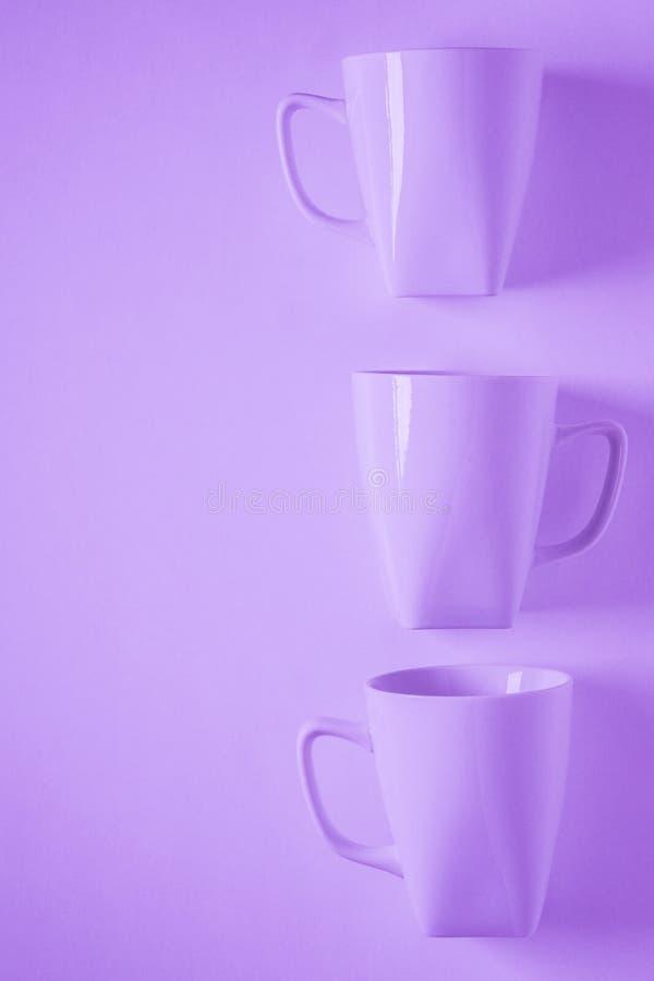 3 purpurrote Kaffeetassen auf purpurartigem Hintergrund in einer vertikalen Reihe, leerer Kopienraum lizenzfreies stockbild