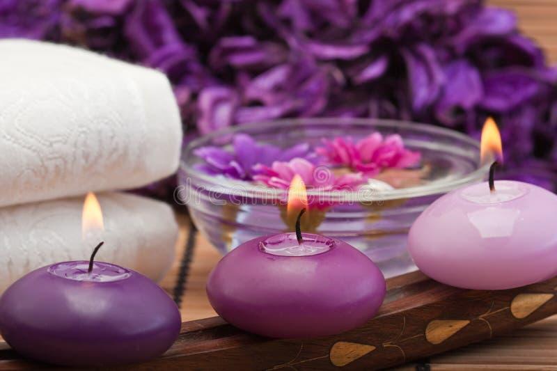 Purpurrote Kerzen und Blumen in Badekurorteinstellung (1) lizenzfreie stockbilder