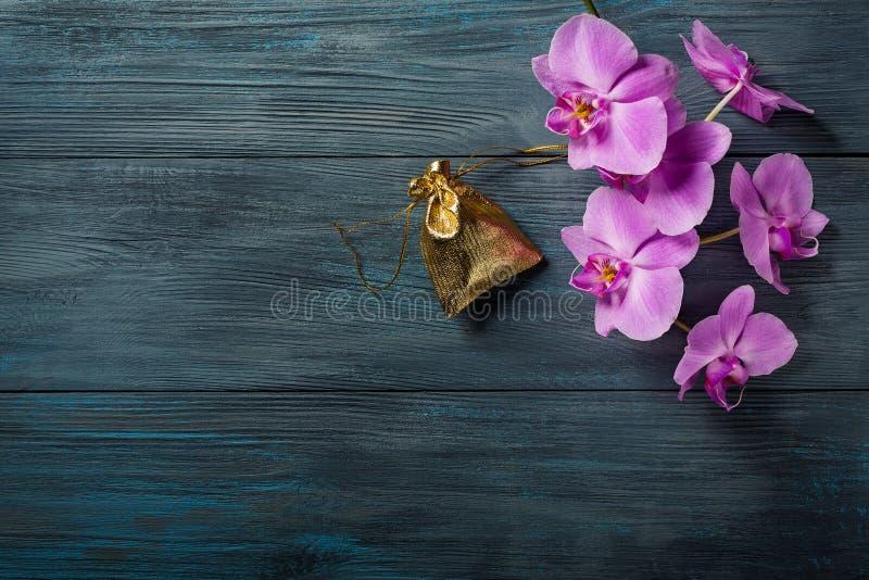 Purpurrote Orchidee und eine Geschenktasche stockfotografie