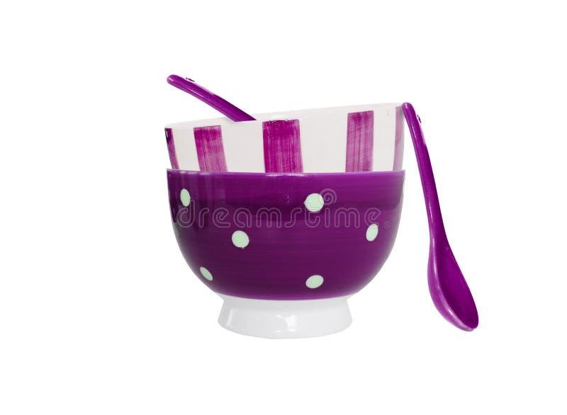 Purpurrote Schüsseln und Löffel auf weißem Hintergrund stockfotos