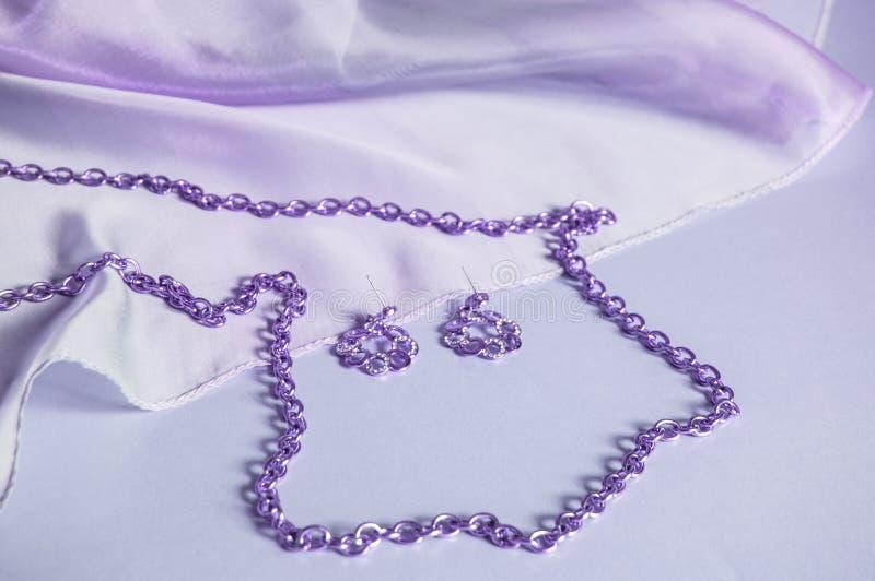 Purpurrote Seide, drapierte Wellen, Silberkette und Ohrringe, getontes Bild in den lila, Luxuszusätzen für Frauen, Hintergrund fü stockbild