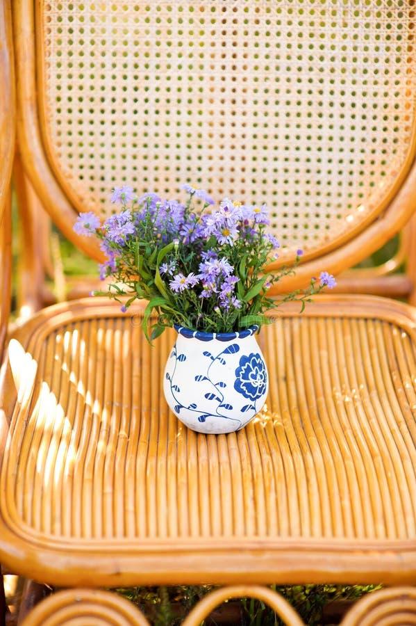 Purpurroter Blumenstrauß in einem geflochtenen Stuhl stockfoto