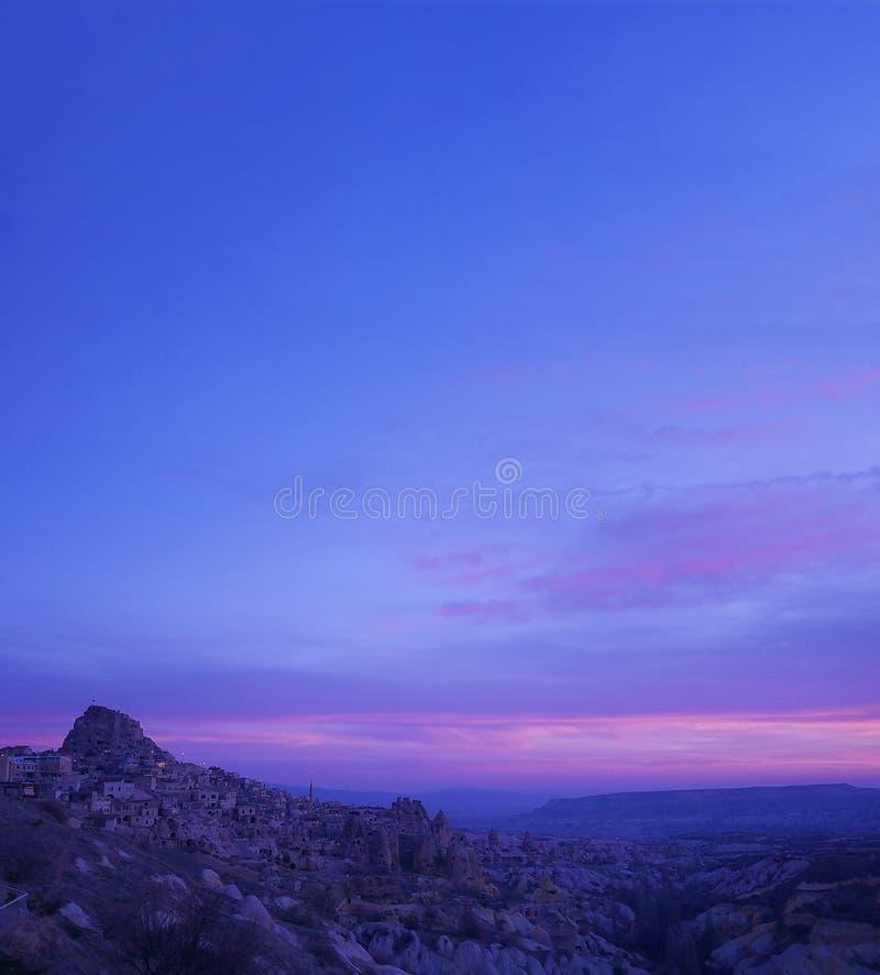 Purpurroter Himmel während des Sonnenaufgangs über Uchisar-Schloss und felsigem Dorf von Cappadocia, eine historische Region in z lizenzfreies stockfoto