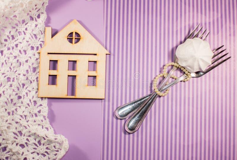 Purpurroter Hintergrund, Haus, zwei Gabeln werden mit Perle verflochten lizenzfreie stockbilder