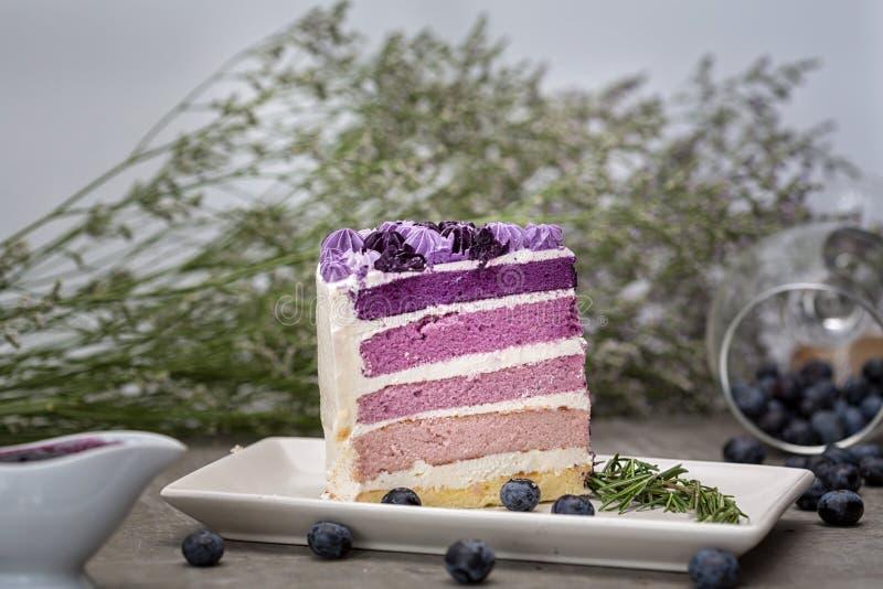 Purpurroter Kuchen mit Zitrone Buttercream wird in mini einzelne Kuchen geschnitten, verzierte mit frischen Brombeeren, für ein s stockbild