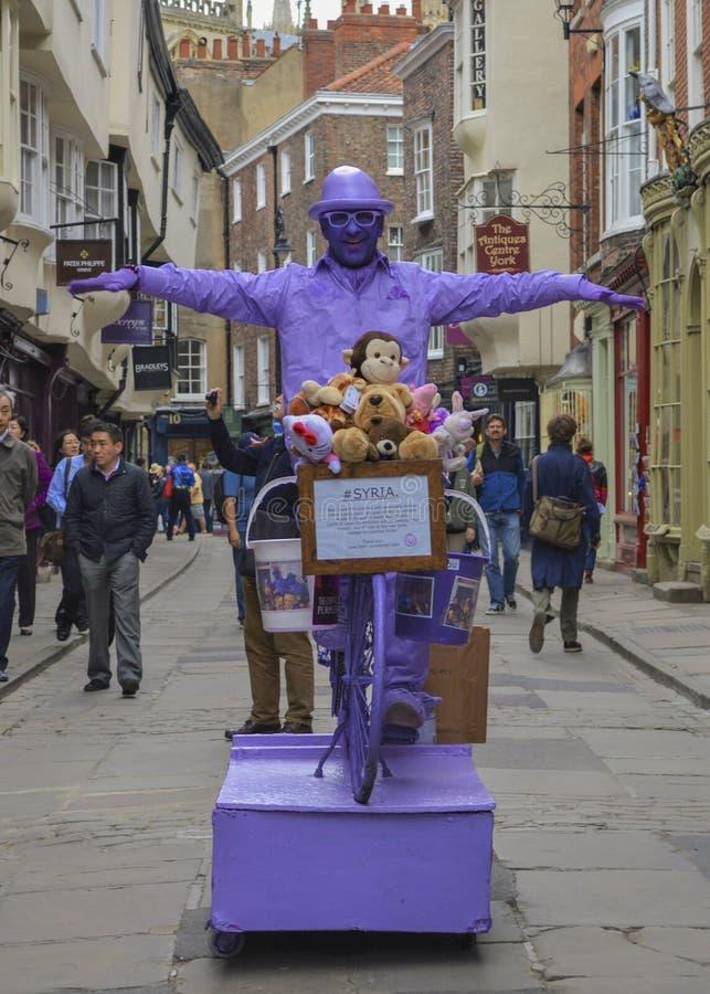Purpurroter Mann-Straßen-Ausführender, Statue, York, England stockfotografie