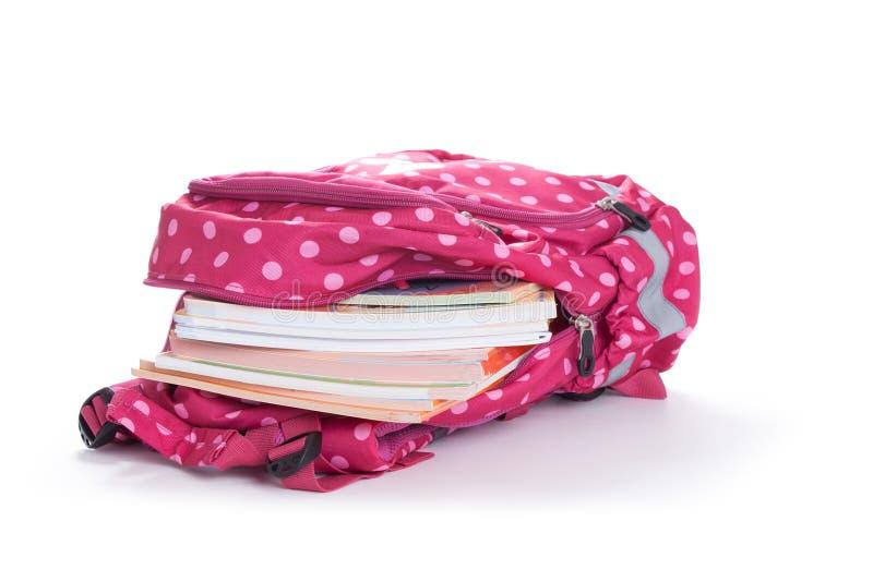 Purpurroter Rucksack mit dem Schulbedarf lokalisiert auf weißem backgroun lizenzfreie stockfotografie