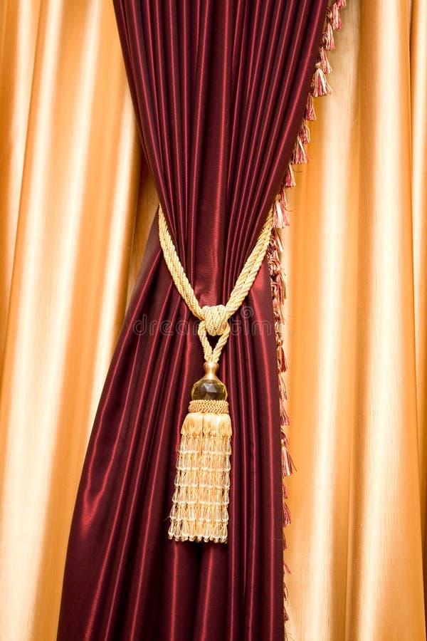 Purpurroter Samttrennvorhang mit goldener Troddel lizenzfreie stockfotos