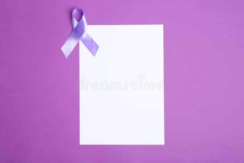 Purpurrotes Bewusstseinsband und leere Karte auf Farbhintergrund, Draufsicht stockbild
