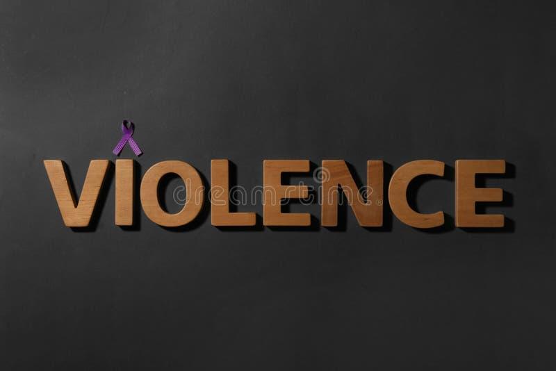 Purpurrotes Bewusstseinsband und Wort GEWALTTÄTIGKEIT gemacht von den hölzernen Buchstaben auf schwarzem Hintergrund stockbild