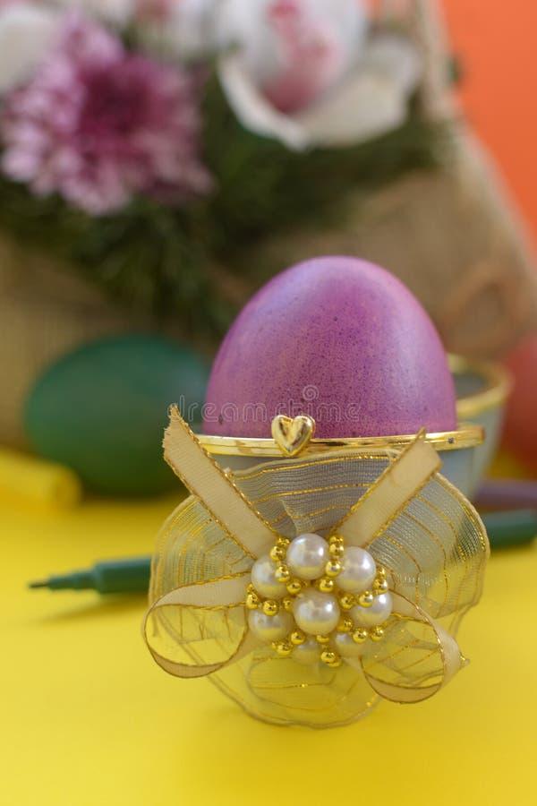 Purpurrotes Ei im Kasten mit goldenem Band lizenzfreies stockfoto