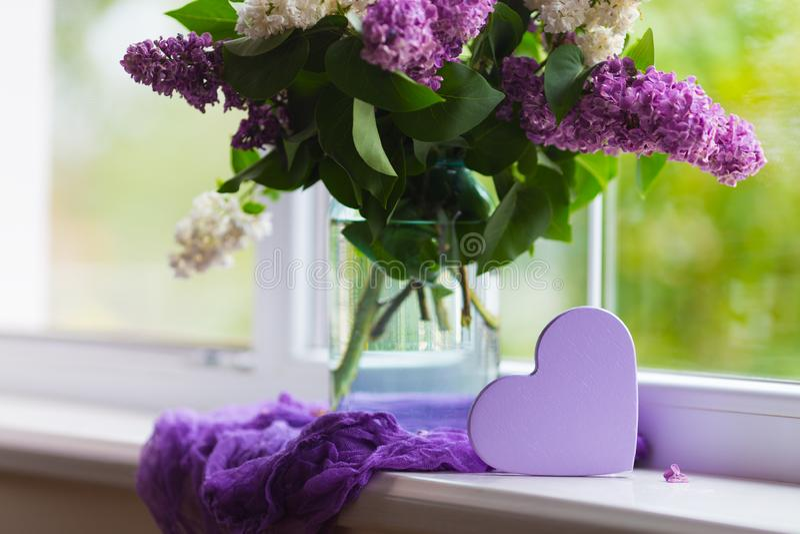 Purpurrotes h?lzernes Herz und zarter Blumenstrau? der sch?nen Flieder im Glasvase nahe Fenster im Tageslicht stockbilder