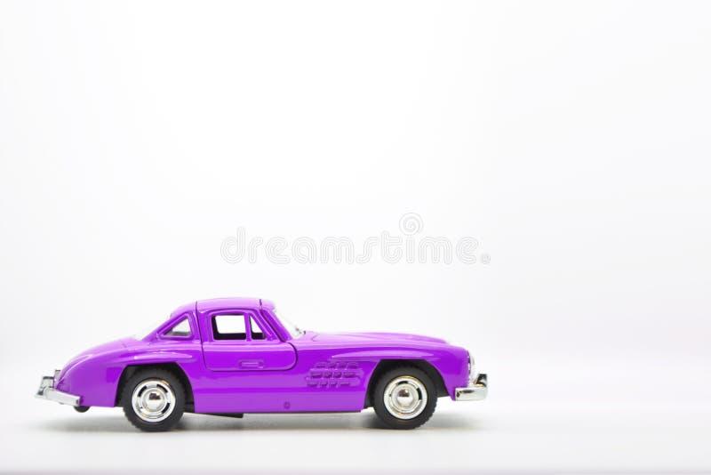 Purpurrotes kleines altes vorbildliches Spielzeugauto lokalisiert auf Hintergrund stockfotografie
