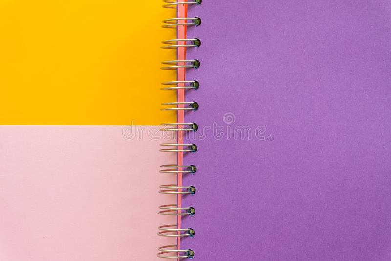 Purpurrotes Notizbuch auf gelbem rosa Pastellhintergrund stockfoto