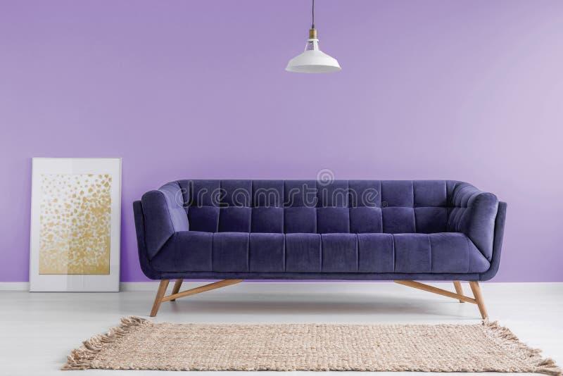 Purpury, aksamitna kanapa i beżowy dywanik w pastelowym lawendowym żywym izbowym wnętrzu z plakatowym egzaminem próbnym, Istna fo zdjęcia stock