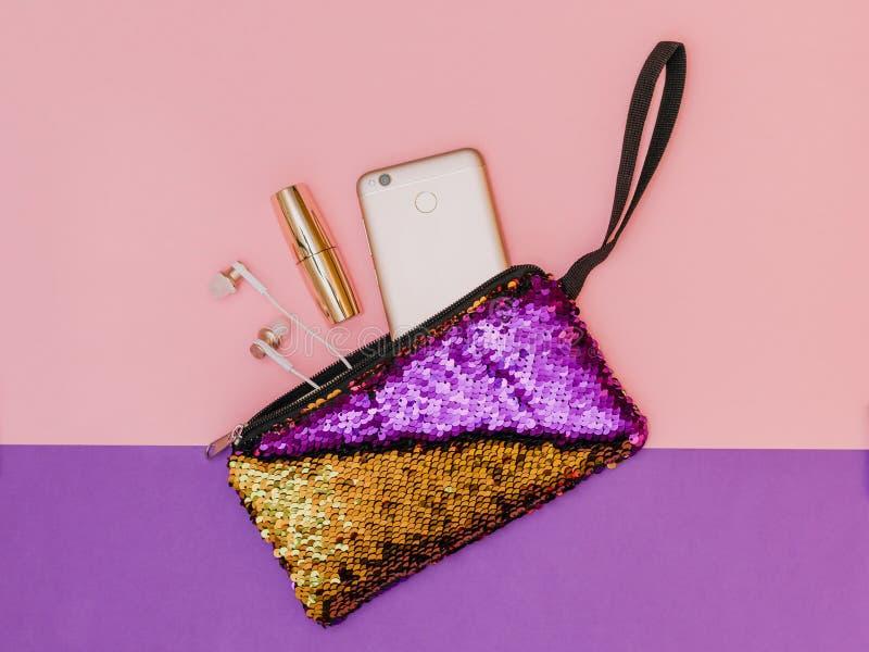 Purpury z złocistą kobiety ` s torebką z telefonem i pomadką na dwa koloru stole Pastelowy kolor Mieszkanie nieatutowy fotografia stock