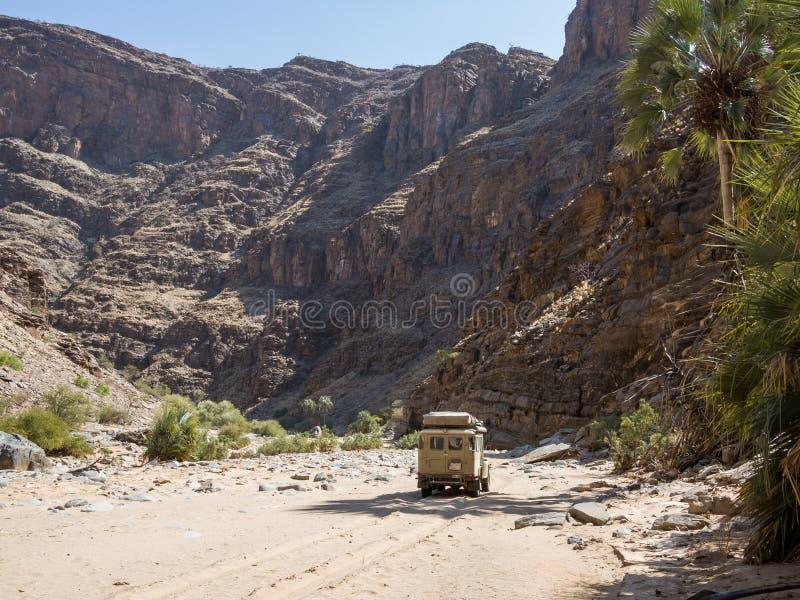 Purros Namibia, Lipiec, - 26, 2015: 4x4 pojazdu offroad jeżdżenie w suchym rzecznym łóżku Hoarusib rzeka z górami obrazy stock