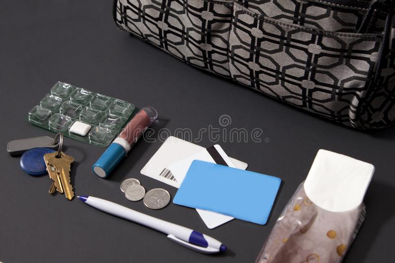 Purse contents side view. Contents of a woman`s purse with lipstick gum cards and keys stock photo