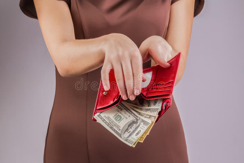 Purse with money in the hands; spending money stock image