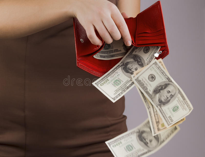 Purse with money in the hands of women, spending money stock image