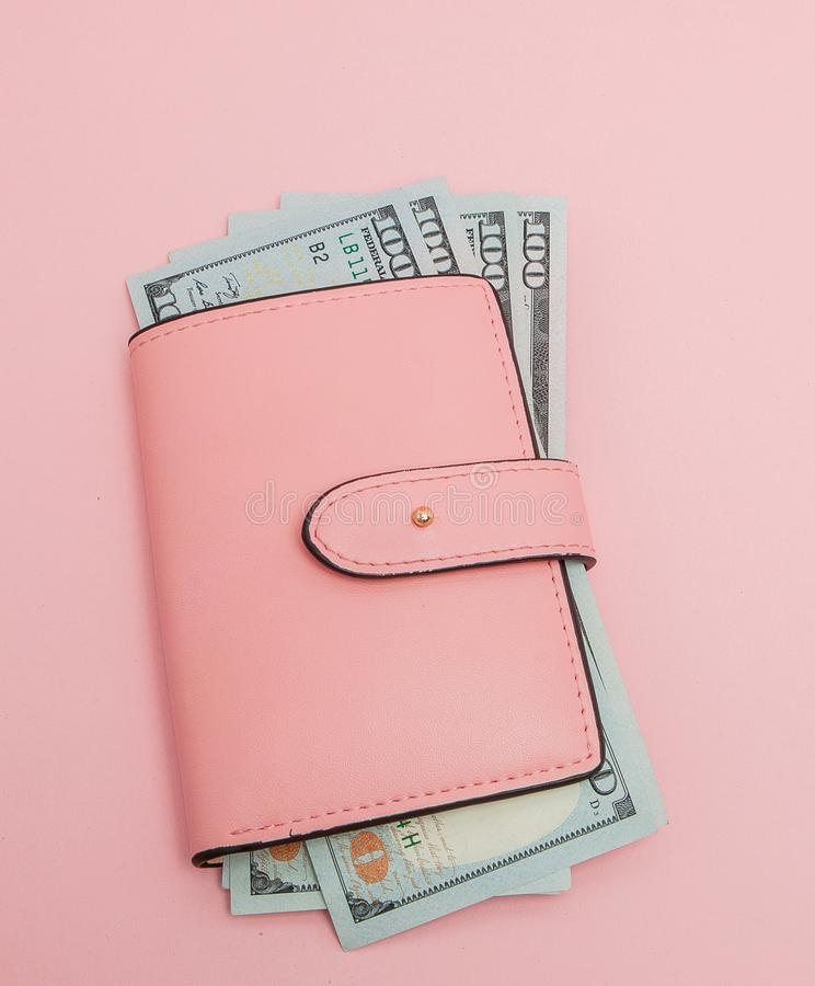 Purse with one hundred dollars banknotes on pink background. Flat lay, top view royalty free stock photos