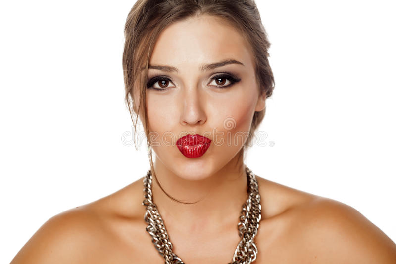 Pursed lips and a necklace. Beautiful young woman with pursed lips and a necklace royalty free stock images