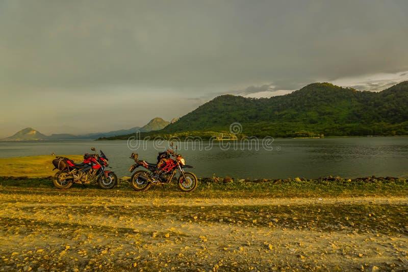 Purwakarta, Zachodni Jawa, Indonezja (03/30/2018): Jeździec objeżdża z jego motocyklem przez Jatiluhur tamy strony która jest zdjęcie stock