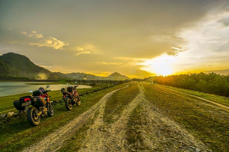Purwakarta, Zachodni Jawa, Indonezja (03/30/2018): Jeździec objeżdża z jego motocyklem przez Jatiluhur tamy strony która jest zdjęcie royalty free
