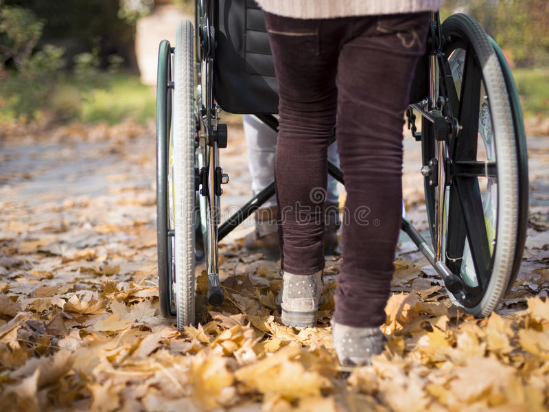 Pusching wheelchair. Person pusching a wheelchair in an autumn day royalty free stock images