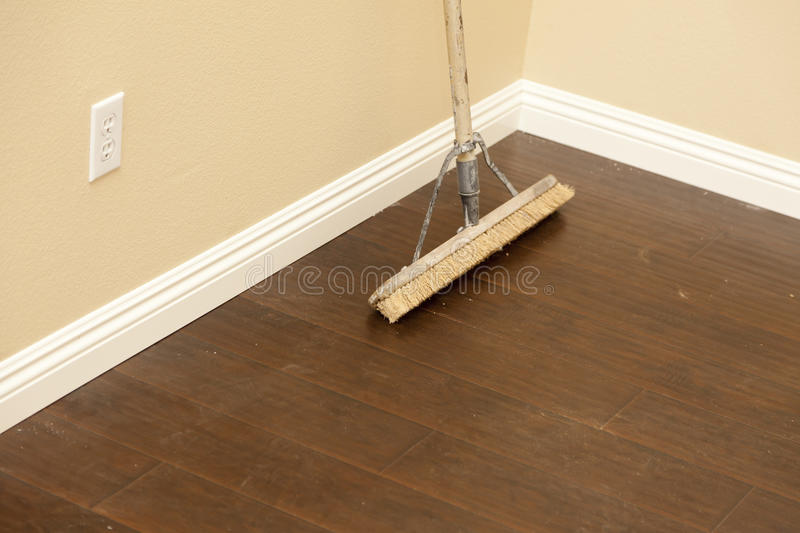 Push Broom on a Newly Installed Laminate Floor and Baseboard royalty free stock photography