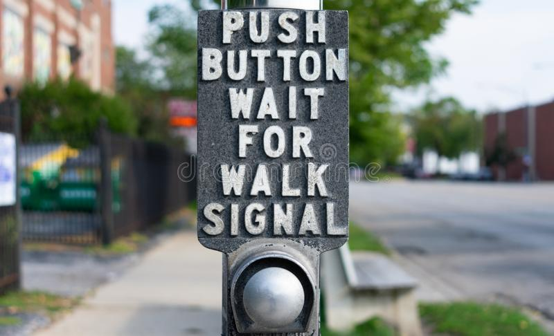 Push Button Wait For Walk Signal Sign at an Urban Street Crossing. A push button wait for walk signal sign at an urban street crossing with a button stock photography