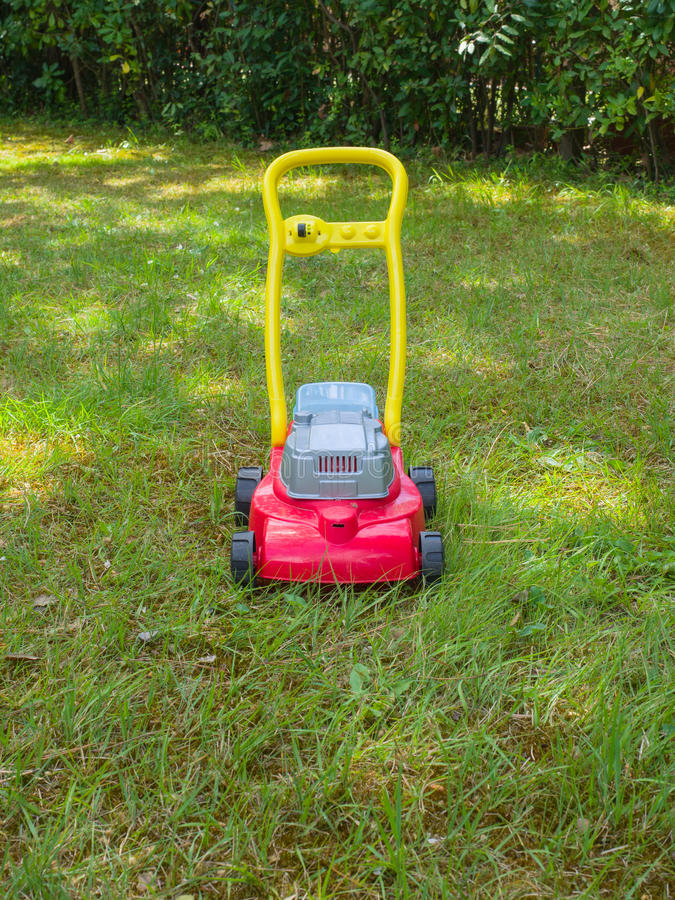 Push lawn mower toy on the grass in a garden . No people. Front view of a Push lawn mower toy in the middle of a garden in a sunny spring day. No people royalty free stock photos