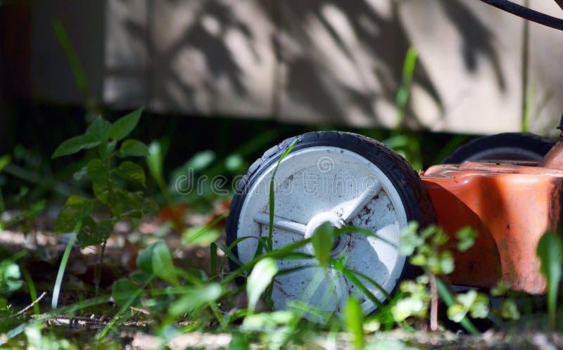 Push Mower Wheel. Red push mower wheel in backyard outdoors stock image