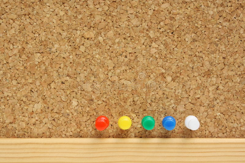 Push Pins. In an organized line on a cork board with copy space stock photos