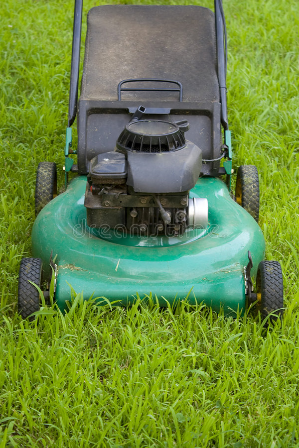 Push Style Lawn Mower. A modern lawn mower cutting through the grass royalty free stock image