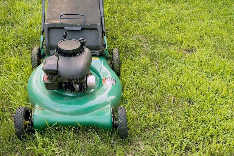 Push Style Lawn Mower. A modern lawn mower cutting through the grass royalty free stock photos
