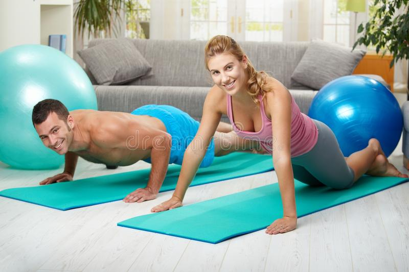 Push up exercise. Young couple doing push up exercise at home in living room