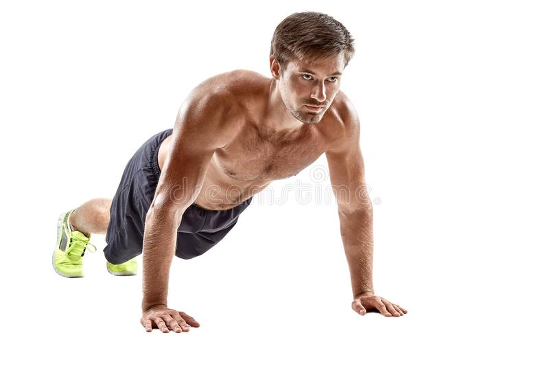 Push up fitness man doing push-up bodyweight exercise on gym floor. Athlete working out chest muscles strength training. Indoors. Horizontal. Copy space stock photography