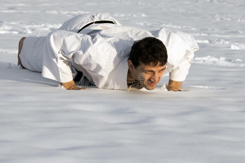 Push up in snow. Man in white kimono barefoot is doing push ups in the snow royalty free stock photos