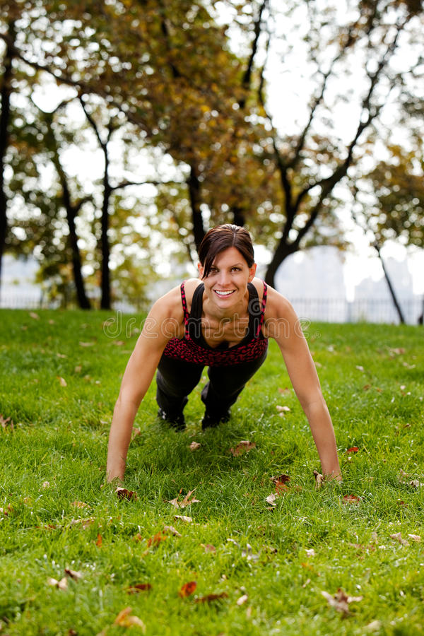 Push Ups. A caucasian female doing push ups in the park royalty free stock photography