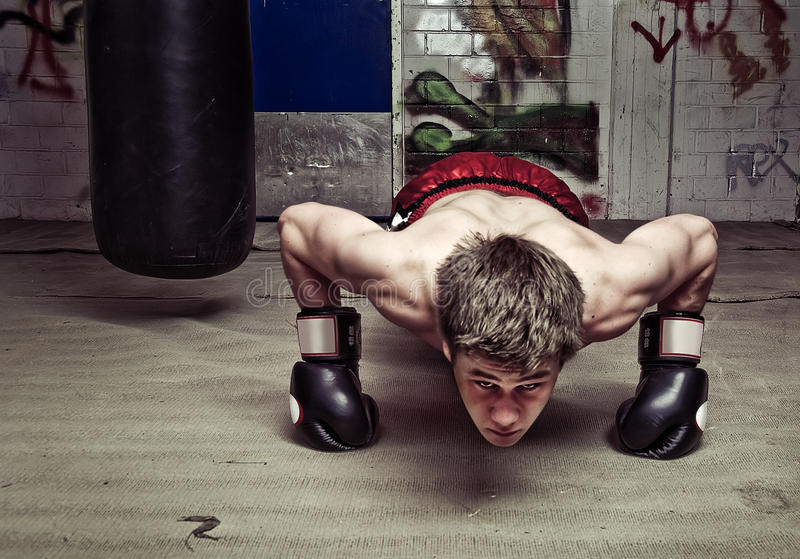 Push-ups. Muscular looking boxer doing press-ups in a graffiti clad suburban basement Focus on the dorsal muscles and biceps stock photos