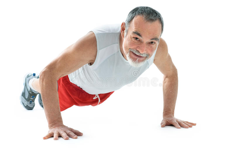 Push-ups. Senior man doing push-ups exercise in gym stock photos