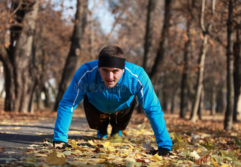 Push-ups. Man doing push-ups outdoor in a park in autumn stock photo