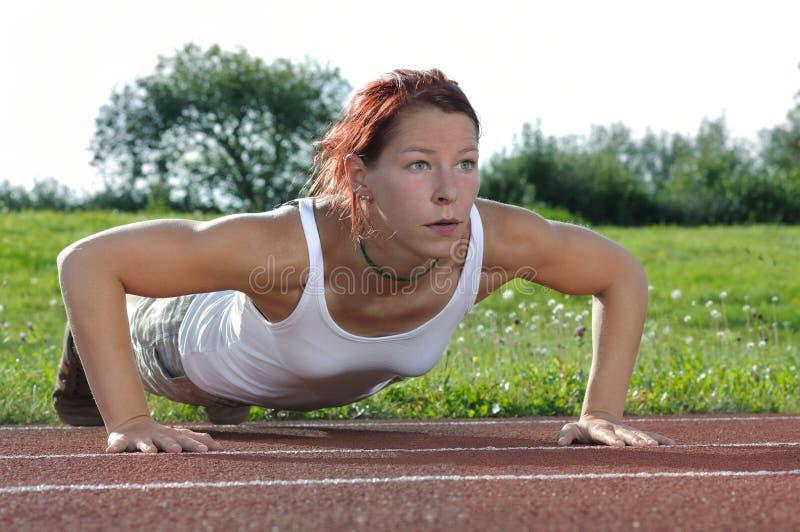 Push-ups. Sporty woman doing push-ups warm-up training on sports field stock image